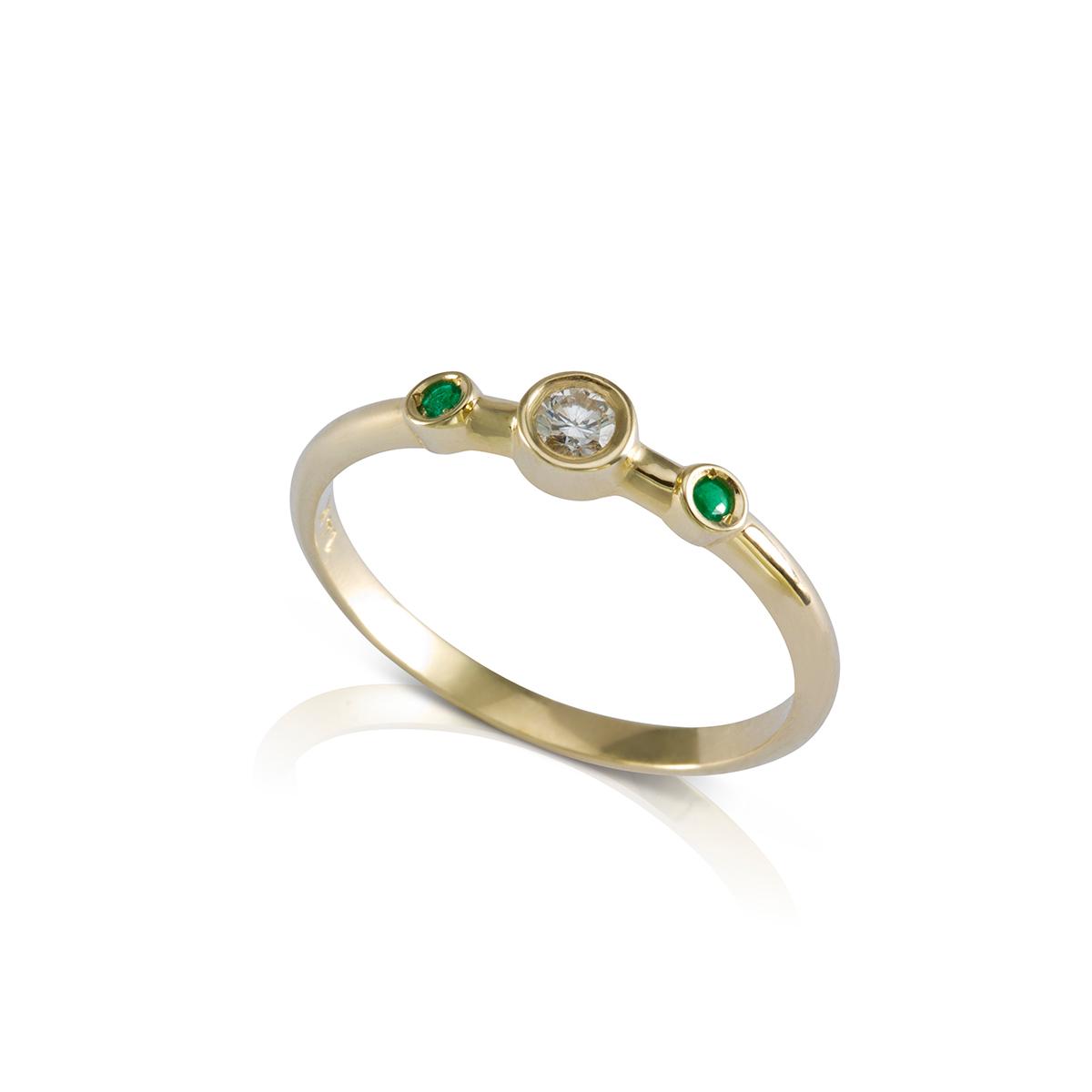A delicate diamond and emerald ring